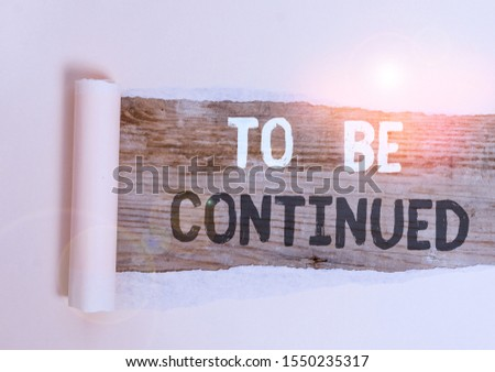 Handwriting text To Be Continued. Concept meaning indicate that the story continues in the next episode Cardboard which is torn in the middle placed above a wooden classic table. #1550235317