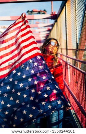 Beautiful blonde woman with American flag in New York. #1550244101