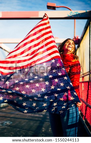 Beautiful blonde woman with American flag in New York. #1550244113