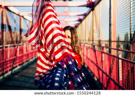 Beautiful blonde woman with American flag in New York. #1550244128