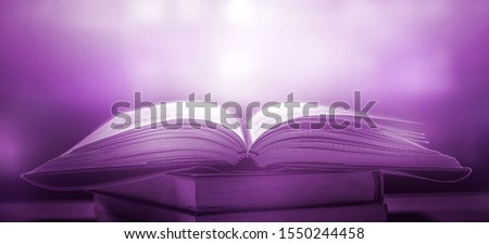 The blurred book that is bewitched with magic, the magic light in the dark, with the bright light shining down as the power to search for knowledge. For research and use as a blurred background #1550244458