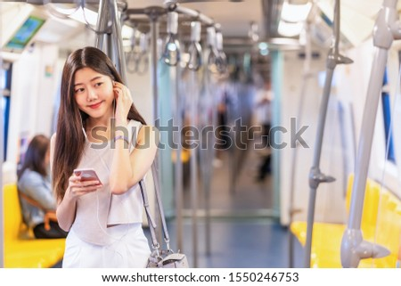 Young Asian woman passenger listening music via smart mobile phone in subway train when traveling in big city,japanese,chinese,Korean lifestyle and daily life, commuter and transportation concept #1550246753