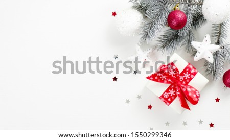 Christmas minimal style banner mockup with Xmas gift wrapped ribbon bow, fir tree branch, festive decorations over white background with confetti stars. Flat lay, top view, copy space #1550299346