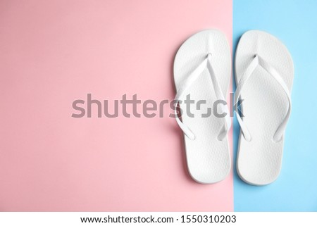 Flat lay composition with flip flops on color background, space for text. Beach objects #1550310203
