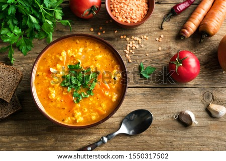 Red Lentil Soup with ingredients on wooden background, top view, copy space. Traditional turkish or arabic lentil and vegetable spicy soup, healthy vegan food. #1550317502