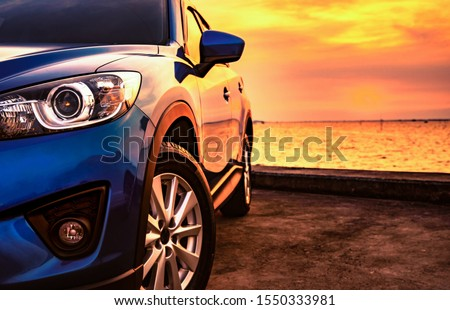Luxury SUV car parked on car parking lot by the beach at sunset. Front view of new SUV car with sport and modern design and beautiful golden sunset sky. Road trip on summer vacation. Electric vehicle. #1550333981