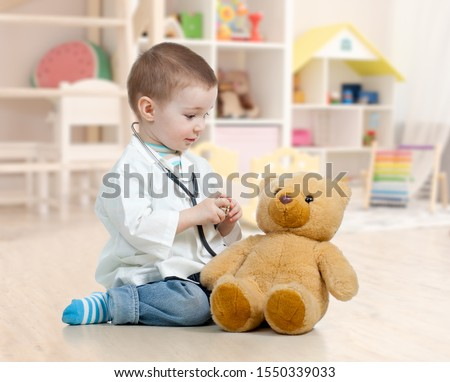 child boy playing doctor and curing plush toy indoors #1550339033