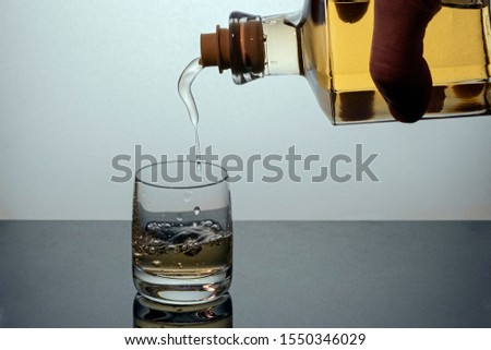the process of pouring strong alcohol from a beautiful glass bottle into a drink glass. liquor is poured over a dark glass surface, alcohol for digestion and health. #1550346029