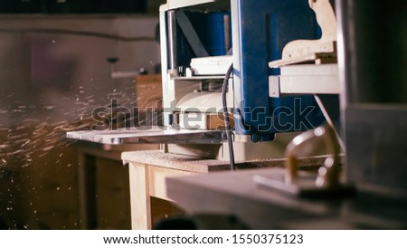 Cabinet planer machine is working with sawdust at wood workshop . Process of work surf gage machine #1550375123