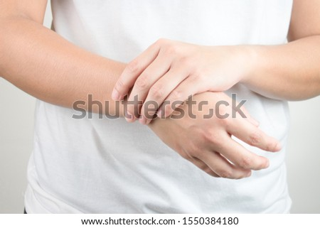 Young hands holding the other side of the wrist. There are wrist injuries that require health care and problems. #1550384180