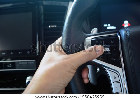 adult hand holding  the steering wheel with  multi media controler button inside of new car passenger room #1550425955