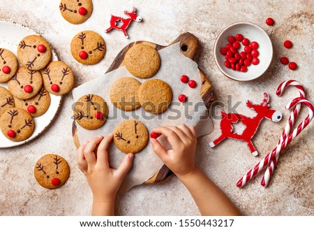 Cooking Christmas gingerbread.  Child's hand decorating red nosed reindeer cookies with chocolate buttons and melted chocolate. Festive homemade decorated sweets #1550443217