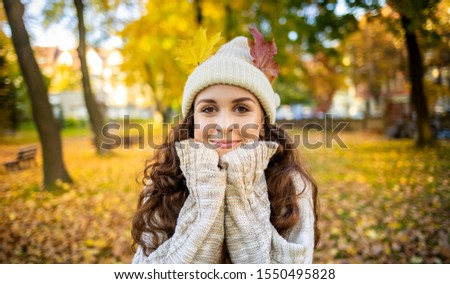 Young smiling woman in city park has colorful autumn leaves in hat and looking at camera #1550495828