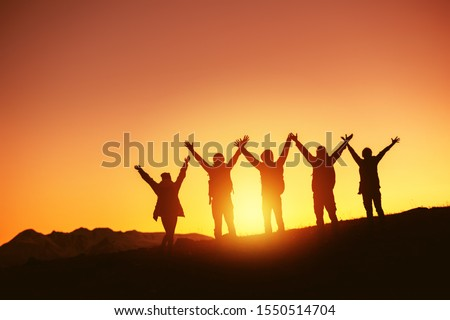 Group of happy peoples silhouettes stands with raised arms against sunset and mountains Royalty-Free Stock Photo #1550514704
