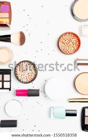 Set of decorative cosmetics mascara powder lipstick eyeshadow blush makeup brush, star confetti on light background top view Flat lay. Beauty blogger concept. Fashion background. Makeup #1550518358
