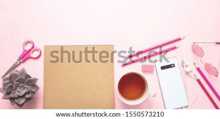 Creative woman office desk. Kraft paper notepad, mobile phone and tea cup against pink background, copy space #1550573210