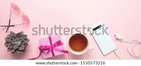 Women day gift, office desk. Gift box, mobile phone and tea cup against pink background, copy space #1550573216