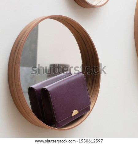 Fashionable beautiful leather small dark wine-colored bag stands on a wooden frame of a round mirror on the wall  in the interior #1550612597