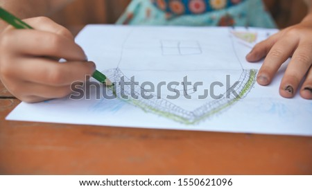 Child draws a pencil drawing of the house and his family. New home. #1550621096