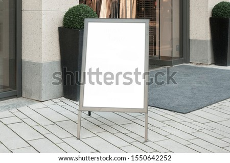 Mockup of the blank white street city outdoor advertising vertical poster stand in silver frame at shop entrance