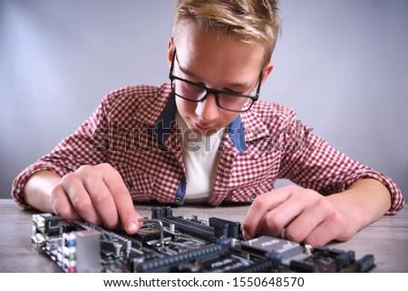 Man repairing broken computer, video card,memory RAM, cooler, processor,hard drive. Young repairer working with screwdriver in service center.teenager  #1550648570