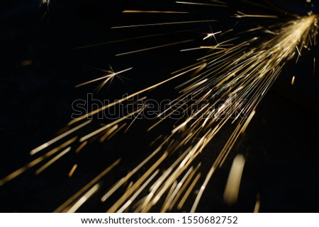 Bright blue and yellow sparks on a black background. Magical lig #1550682752