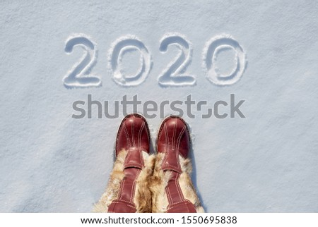 Concept picture.inscription New Year 2020 and footprints in the snow