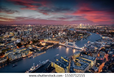 Aerial view of illuminated London, UK, during evening time featuring the Tower Bridge, Thames river and the modern skyscrapers of Canary Wharf #1550712155
