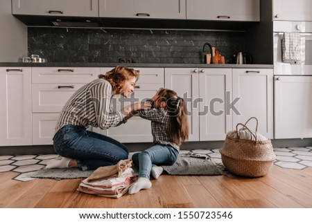 Little girl covered her eyes while playing with her beloved mother in kitchen #1550723546