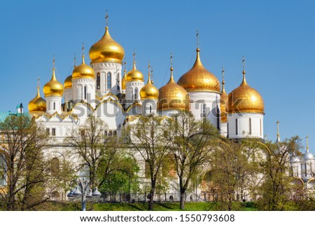 Moscow, Russia - May 01, 2019: View of orthodox churches with white walls of Moscow Kremlin against green trees in sunny spring morning #1550793608
