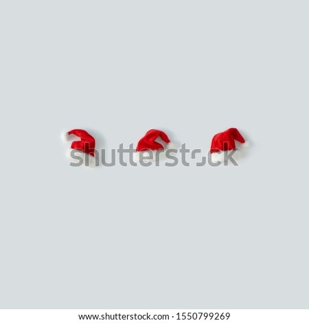 Creative Santa Claus hat with bright background. Minimal winter flat lay Christmas concept.