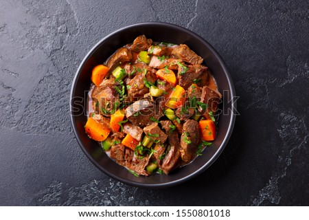 Beef meat and vegetables stew in black bowl. Slate background. Top view. #1550801018