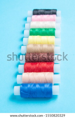 colored spools of sewing thread on a blue background #1550820329