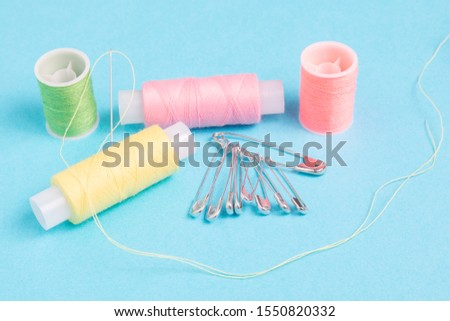 colored spools of sewing thread on a blue background #1550820332
