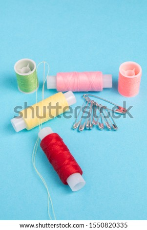 colored spools of sewing thread on a blue background #1550820335
