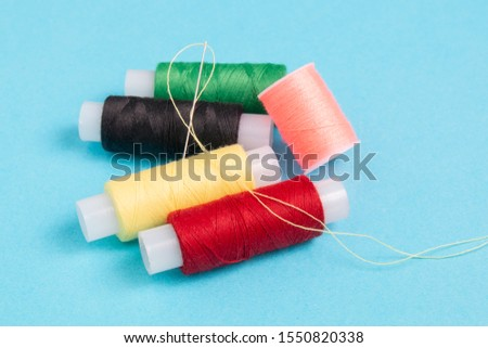colored spools of sewing thread on a blue background #1550820338