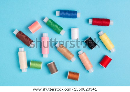 colored spools of sewing thread on a blue background #1550820341
