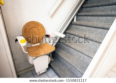 Automatic stair lift on staircase taking elderly people and disabled persons up and down in a house close-up #1550831117