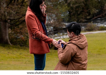 Will you marry me traditional kneeling proposal, happy attractive Asian couple fall in love make proposal to get married engagement with diamond ring in Autumn landscape, beautiful woman crying tears  #1550832605