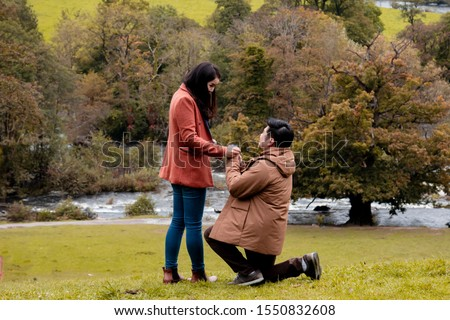 Will you marry me traditional kneeling proposal, happy attractive Asian couple fall in love make proposal to get married engagement with diamond ring in Autumn landscape, beautiful woman crying tears  #1550832608