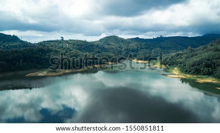 Mountain view with reflection on the lake, have cloudy sky in cinematic tone #1550851811