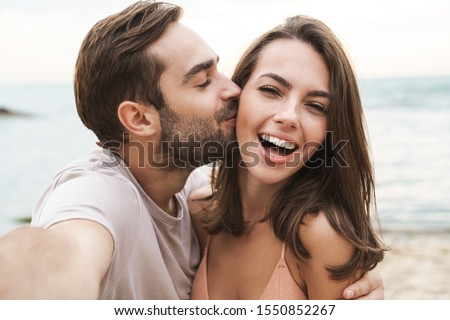 Image of young happy man kissing and hugging beautiful woman while taking selfie photo on sunny beach #1550852267