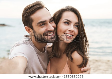 Photo of smiling young couple hugging and taking selfie photo while resting on sunny beach #1550852273