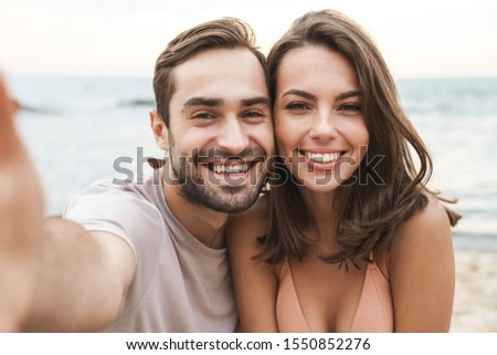 Photo of joyful young couple smiling and taking selfie photo while resting on sunny beach #1550852276