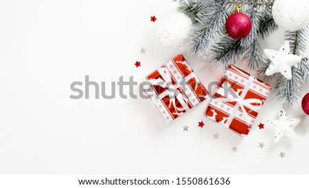 Christmas tree branch with balls and gifts on white background with copy space. Flat lay, top view. Winter holidays postcard template, Xmas banner mockup, New year greeting card #1550861636