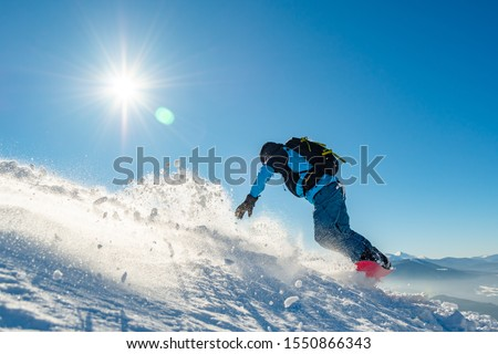 Snowboarder Riding Red Snowboard in the Mountains at Sunny Day. Snowboarding and Winter Sports #1550866343