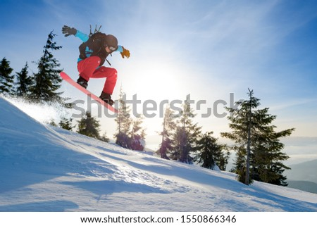 Snowboarder Jumping on the Red Snowboard in the Mountains at Sunny Day. Snowboarding and Winter Sports #1550866346