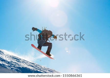 Snowboarder Jumping on the Red Snowboard in the Mountains in Bright Rays of Sun. Snowboarding and Winter Sports #1550866361