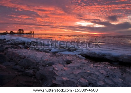 Sunset-colored winter coastl landscape with the freezing Baltic Sea in Estonian seacoast #1550894600