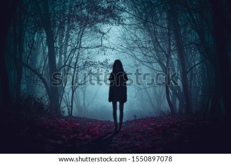 Ghost on the scary road in the paranormal world. Horrible dream. Strange forest in a fog. Mystical atmosphere. Dark wood. Mysterious road. Gothic witch. Background wallpaper. Gloomy times.  #1550897078